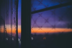 Amazing romantic sunset in window behind silhouettes of tulle texture. Wonderful orange violet blue dawn sky from window through patterned curtain. Cosiness background of scenic sunrise. Copy space.