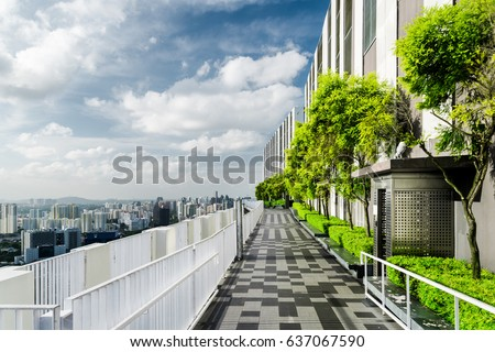 Amazing rooftop garden. Beautiful outside terrace with park and scenic city view. Modern benches under green trees along walkway. Urban eco design and mini-ecosystem. Landscaping in Singapore. #637067590