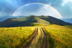 Amazing scene in summer mountains. Lush green grassy meadows in fantastic evening sunlight. Rural road and beautyful rainbow in dramatic sky. Landscape photography