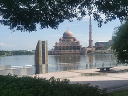 Amazing scene surrounding the lake infront of Putrajaya Mosque with beautiful cluds and blue sky.