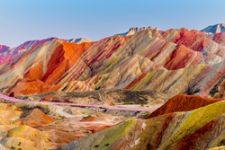 Amazing scenery of Rainbow mountain and blue sky background in sunset. Zhangye Danxia National Geopark, Gansu, China. Colorful landscape, rainbow hills, unusual colored rocks, sandstone erosion