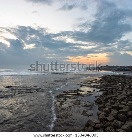 Amazing scenic seashore with wave and stones at sunset in the dusk on Bali Island in Indonesia