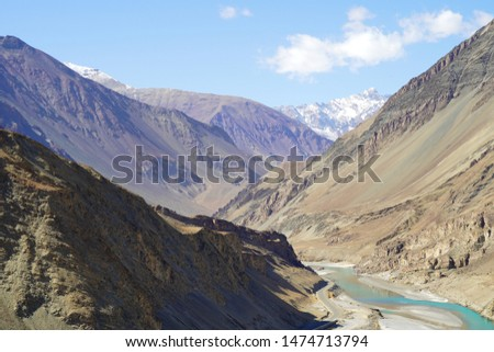 Amazing scenic view of high mountain road in rugged rock covered with melting snow against the background of dramatic blue sky, Leh district, Ladakh range, Himalayas, Jammu & Kashmir, Northern India #1474713794