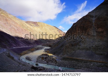 Amazing scenic view of high mountain road in rugged rock covered with melting snow against the background of dramatic blue sky, Leh district, Ladakh range, Himalayas, Jammu & Kashmir, Northern India #1474713797