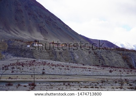 Amazing scenic view of high mountain road in rugged rock covered with melting snow against the background of dramatic blue sky, Leh district, Ladakh range, Himalayas, Jammu & Kashmir, Northern India #1474713800