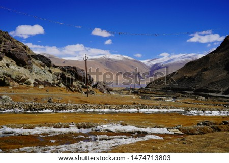 Amazing scenic view of high mountain road in rugged rock covered with melting snow against the background of dramatic blue sky, Leh district, Ladakh range, Himalayas, Jammu & Kashmir, Northern India #1474713803