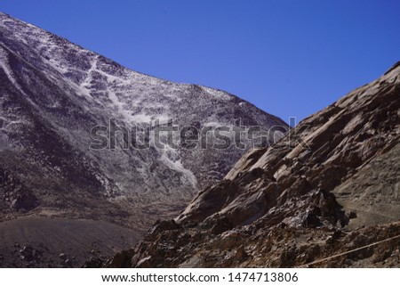 Amazing scenic view of high mountain road in rugged rock covered with melting snow against the background of dramatic blue sky, Leh district, Ladakh range, Himalayas, Jammu & Kashmir, Northern India #1474713806
