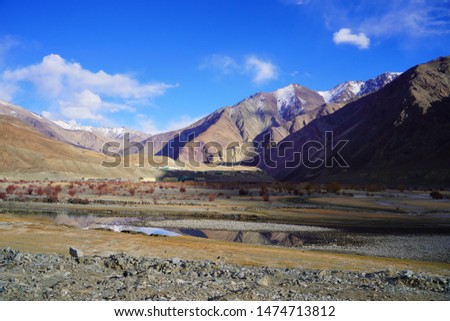 Amazing scenic view of high mountain road in rugged rock covered with melting snow against the background of dramatic blue sky, Leh district, Ladakh range, Himalayas, Jammu & Kashmir, Northern India #1474713812