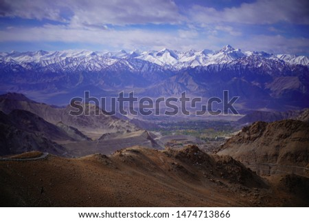 Amazing scenic view of high mountain road in rugged rock covered with melting snow against the background of dramatic blue sky, Leh district, Ladakh range, Himalayas, Jammu & Kashmir, Northern India #1474713866
