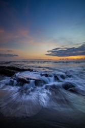 Amazing seascape for background. Beach with rocks and stones. Low tide. Motion water. Colorful sky with clouds. Slow shutter speed. Soft focus. Mengening beach, Bali, Indonesia. Vertical layout.