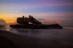 Amazing seascape. Sunrise at Yeh Gangga beach. Rock in the ocean. Natural hole in rock formation. Waves captured with slow shutter speed. Long exposure, soft focus. Landscape background. Tabanan, Bali
