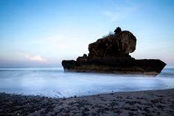 Amazing seascape. Sunrise at Yeh Gangga beach. Rock in the ocean. Waves captured with slow shutter speed. Long exposure with soft focus. Landscape background. Tabanan, Bali, Indonesia