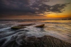 Amazing seascape with motion waves. Waterscape background. Moving water. Nature concept. Sunset scenery background. Beach with stones and rocks. Long exposure. Soft focus. Mengening beach, Bali.