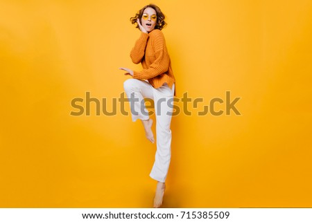 Amazing short-haired woman in trendy sweater standing on one leg and propping face with hand. Indoor full-length portrait of enthusiastic barefooted girl wears white pants.