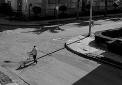 Amazing shot of a lonely man pushes an empty market car across the empty street of a neighborhood, due to obligatory quarantine by Coronavirus or covid-19 global pandemic. Black and white photography.