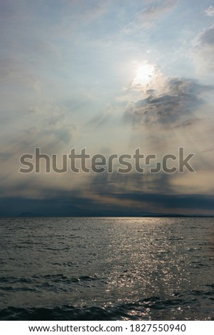Amazing  sky with rising sun over the lake Garda, Italy. Dark clouds and sunlights.