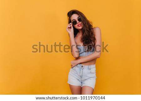 Amazing slim lady in casual outfit standing in confident pose on yellow background. Indoor photo of lovely girl with long dark hair sensually posing. #1011970144