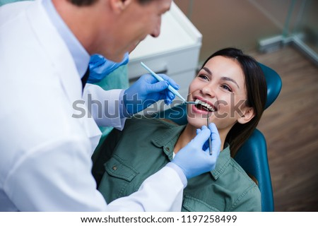 Amazing smile! Top view of dentist examining his beautiful patient in dentist's office