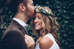 Amazing smiling wedding couple. Pretty bride and stylish groom.