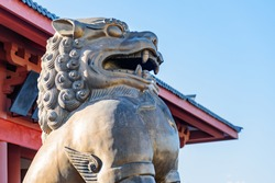 Amazing statue of mystical Chinese guardian lion on red roof background in Dali Old Town, Yunnan province, China. The ancient town is a popular tourist destination in Asia.