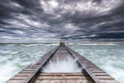 Amazing storm coming from the sea with waves brake over the board walk