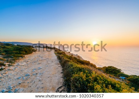 Amazing stunning unbelievable sunset at atlantic ocean in Portugal. Cape Rock fantasy seascape. View from big height at colorful scenic sea with rocks and mountains in evening. Tropical paradise. #1020340357