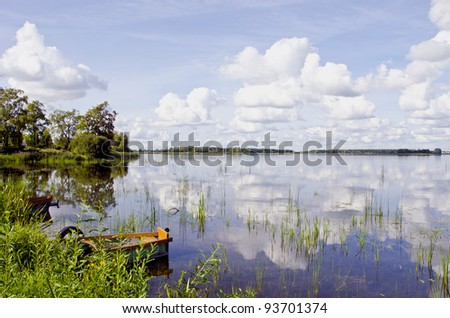 Amazing summer lake landscape, Boats on coast, clouds in sky and reflections on water. - stock photo