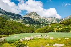 Amazing summer mountain landscape with river, lush green vegetation, beautiful mountain peak and blue sky with white clouds in the background, Muratov peak, Pirin mountain, Bulgaria.