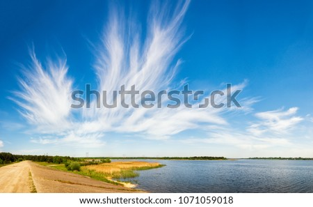 Amazing summer scenery of picturesque lake with reeds on foreground, beautiful cirrus fibratus clouds in the blue sky and dirt road through the dam in countryside.