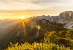 Amazing sunrise in the mountains. Backlight Sunlight with beautiful lens flares and sunbeams. Julian Alps, Triglav National Park, Slovenia, Mountain Slemenova, Sleme.