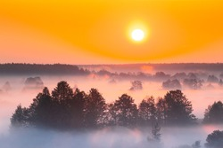 Amazing Sunrise Over Misty Landscape. Scenic View Of Foggy Morning Sky With Rising Sun Above Misty Forest And River. Early Summer Nature Of Eastern Europe. Sunset Dramatic Sunray Light Sunbeam.