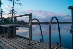 Amazing sunset at the bog lake. Nice  platform for going for a swim. Small ladder for getting out of the cold early spring swamp lake. Colorful clouds in the sky which reflect from the water.