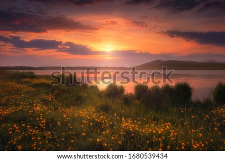 Photo of  Amazing sunset by the lake. Colorful sky with beautiful rays. Warm sunny evening at the mountain lake