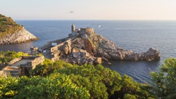 Amazing sunset in the Gulf of Poets. Beautiful landscape of Porto Venere in Italy. Ruins of Doria Castle, church of Saint Peter on a steep cliff, small Palmaria Island, Mediterranean sea and seagulls.