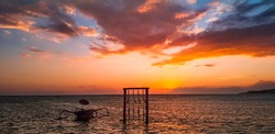 Amazing sunset on Gili Air Island with silhouette of swing and boat in the water. Colorful evening on the beach in a top popular tropical destination in Bali, Indonesia.