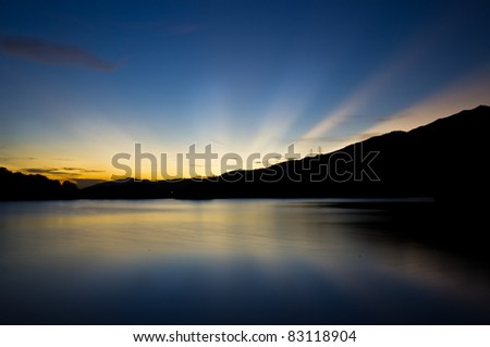 amazing sunset on water with radial yellow light on blue sky