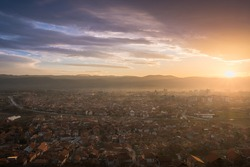 Amazing sunset over a city lighten by last sunrays, hazy atmosphere and beautiful soft light under a colorful sky