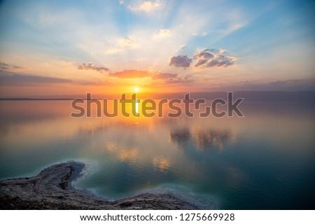 Amazing sunset over Dead sea, view from Jordan to Israel and Mountains of Judea. Madaba governorate and Karak governorate. Reflection of sun, skies and clouds. Salty beach, salt on Dead sea coast. #1275669928