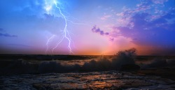 Amazing sunset over the stormy sea thunder and lightning in the background