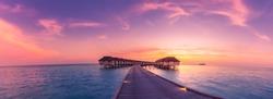 Amazing sunset panorama at Maldives island. Luxury resort villas seascape with soft led lights under colorful sky.