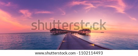 Amazing sunset panorama at Maldives island. Luxury resort villas seascape with soft led lights under colorful sky.