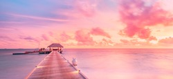 Amazing sunset panorama at Maldives. Luxury resort villas seascape with soft led lights under colorful sky. Tranquil seascape with jetty and tropical travel or vacation mood, endless horizon view