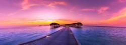 Amazing sunset panorama at Maldives. Luxury resort villas seascape with soft led lights under colorful sky.