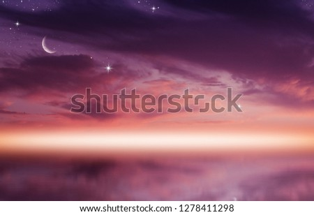 Amazing sunset picture with fluffy clouds, crescent moon against bright rays of sun reflected on the water surface.