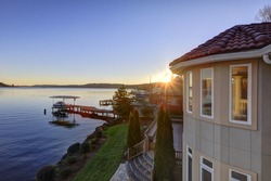 Amazing sunset view of Lake Washington and private dock from the upper balcony of luxurious Mediterranean style waterfront home. Northwest, USA