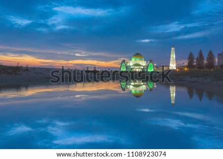 Amazing sunset with beautiful lights at a mosque by a beach at Malacca, Malaysia with reflection in water. #1108923074