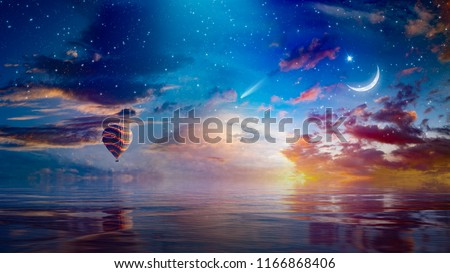 Amazing surreal background - crescent moon and hot air balloon rising above serene sea in sunset sky, glowing horizon and comet. Elements of this image furnished by NASA #1166868406