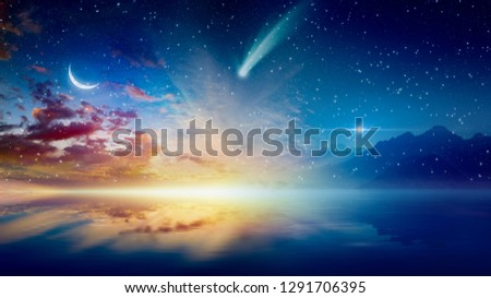 Amazing surreal background - crescent moon, glowing horizon, bright stars and comet above serene sea. Elements of this image furnished by NASA #1291706395