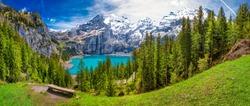 Amazing tourquise Oeschinnensee with waterfalls and Swiss Alps, Kandersteg, Berner Oberland, Switzerland.