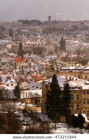 Amazing towers of Charles bridge and old town district during winter day. Heavy snow storm and sun rays peeping through clouds, Prague, Czech republic #473211844